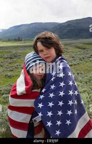 Brother and sister wrapped in American flag in field - Stock Photo
