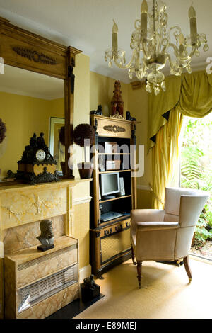 Mirror above fireplace with gas fire in traditional  study with armchair at classical style cabinet with small computer - Stock Photo