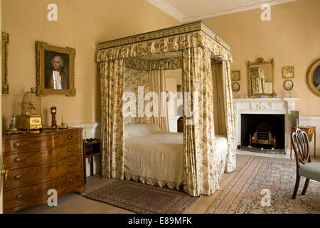 Floral drapes and canopy on four poster bed in country house bedroom - Stock Photo