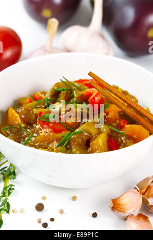 Delicious eggplant food with tomato, sweet pepper and fresh herbs close up. - Stock Photo