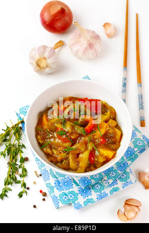 Delicious eggplant stew with tomato, sweet pepper, fresh herbs, onion and garlic. Top view. - Stock Photo