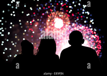 President Barack Obama, First Lady Michelle Obama, and Malia Obama, center, watch the Fourth of July fireworks from the roof of Stock Photo