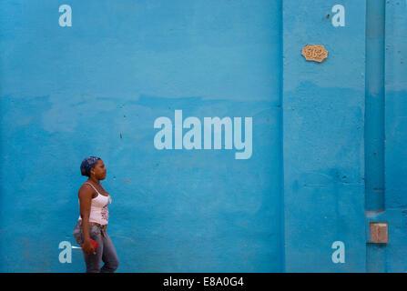 Local woman walking past a blue wall, Old Havana, Havana, Cuba - Stock Photo