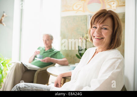 Portrait of senior woman smiling while mature man in background - Stock Photo
