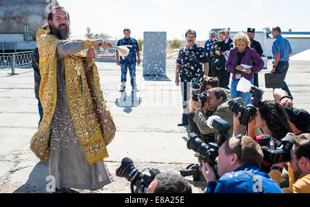 An Orthodox priest blesses members of the media at the Baikonur Cosmodrome launch pad on Wednesday, September 24, - Stock Photo
