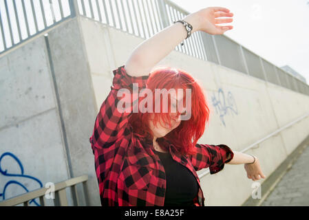Young teenage girl dancing red dyed hair