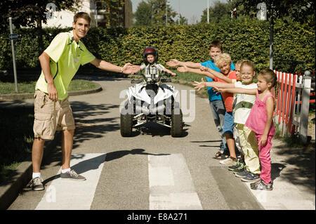 Tutor and children at zebra crossing - Stock Photo