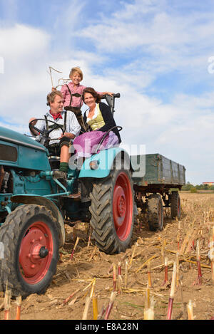 Family on tractor in cornfield, Bavaria, Germany - Stock Photo