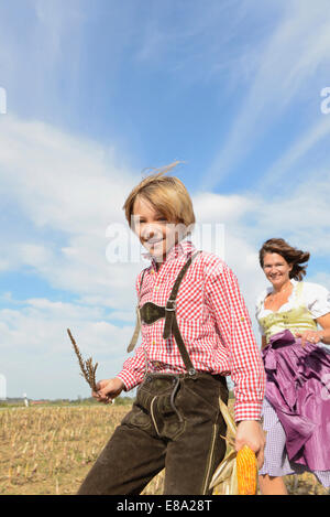 Mother and son running in cornfield, Bavaria, Germany - Stock Photo
