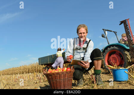 Mature man checking digital tablet in front of basket with apples, woman and son in background, Bavaria, Germany