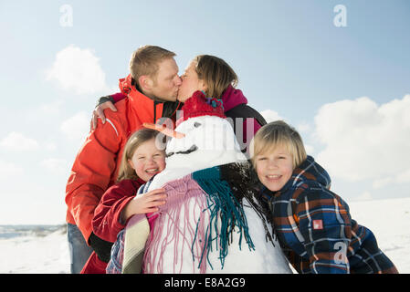 Girl and boy standing with snowman, parents kissing in background, Bavaria, Germany - Stock Photo