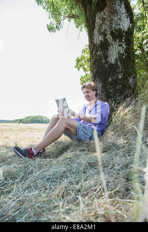 Mid adult man sitting under tree and using digital tablet - Stock Photo
