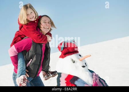 Mother giving piggyback ride to daughter, smiling, Bavaria, Germany - Stock Photo