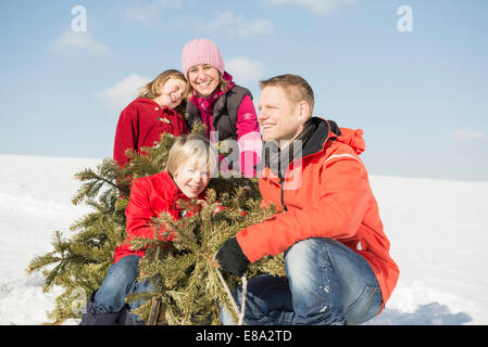 Family sitting with branches in winter, smiling, Bavaria, Germany - Stock Photo