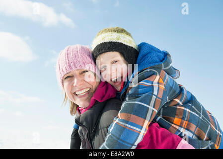Mother giving piggy back ride to son, smiling, portrait, Bavaria, Germany - Stock Photo