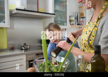 Boy helping his mother to pepper salad - Stock Photo