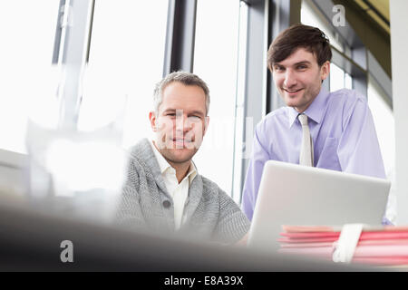 Businessmen using laptop in office, smiling - Stock Photo