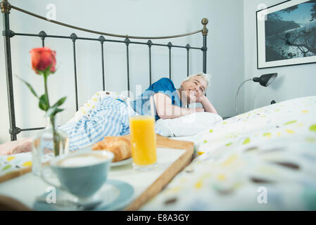 Breakfast tray on bed while mature man in background - Stock Photo