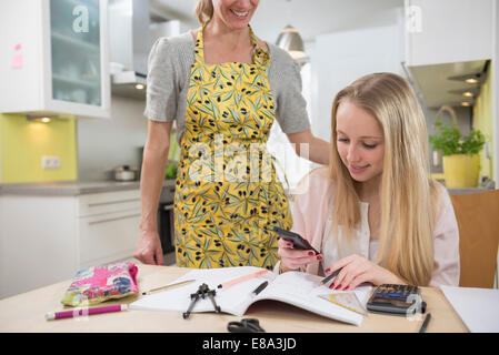 Mother helping daughter with homework, smiling - Stock Photo