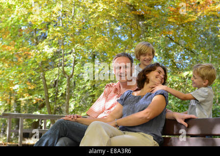 Family playing around bench, smiling, Bavaria, Germany - Stock Photo