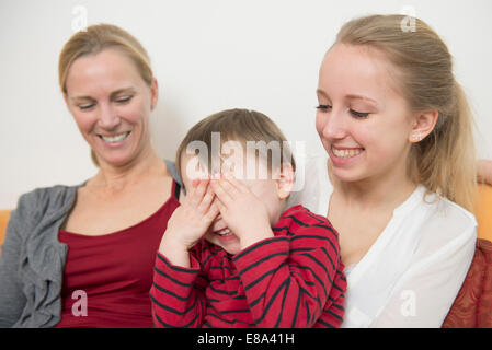 Mother with her daughter while son covering eyes, smiling - Stock Photo