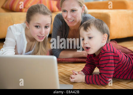 Family using laptop in living room, smiling - Stock Photo