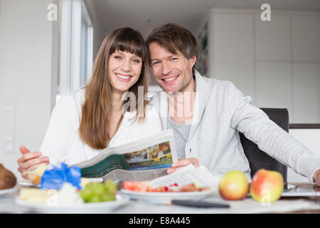 Portrait of couple having breakfast and reading newspaper together, smiling - Stock Photo