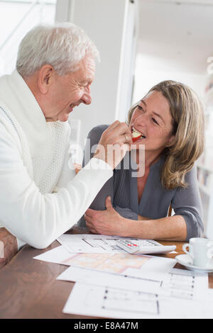 Happy senior man feeding woman with apple slices - Stock Photo