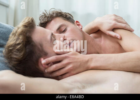 Homosexual couple caress each other in bed, close up - Stock Photo