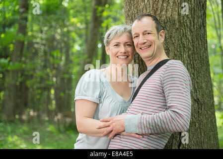 Portrait of mature couple leaning by tree in forest, smiling - Stock Photo