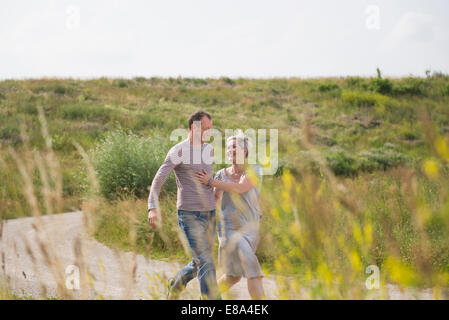 Mature couple running on field in summer, smiling - Stock Photo