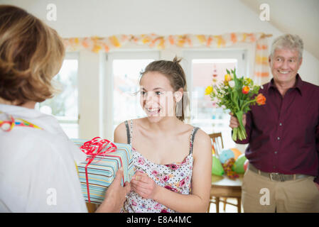 Granddaughter handover present to her grandmother while grandfather waiting with bouquet - Stock Photo