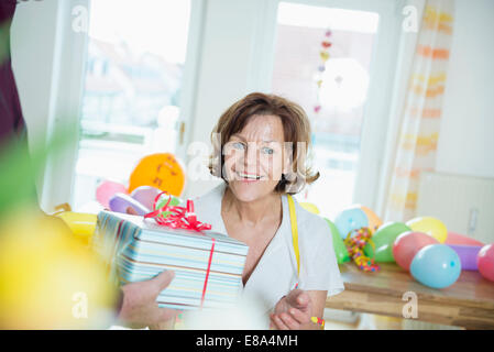 Senior man hand over present to woman on birthday, smiling - Stock Photo