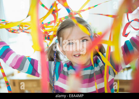 Portrait of girl with blowout paper streamer at birthday party, smiling - Stock Photo
