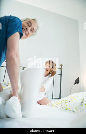 Couple having pillow fight in bed, smiling - Stock Photo