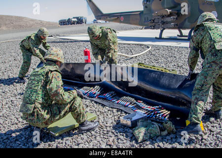 Japan Ground Self-Defense Force soldiers prepare ammunition to be loaded into the 20 mm cannon of an AH-1S Cobra helicopter Sept. 4, 2014, during Rising Thunder 2014 at the Yakima Training Center in Washington. Rising Thunder is a U.S. Army-hosted exercis Stock Photo