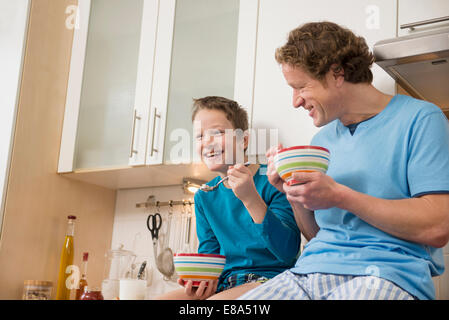 Father and son eating muesli in kitchen - Stock Photo