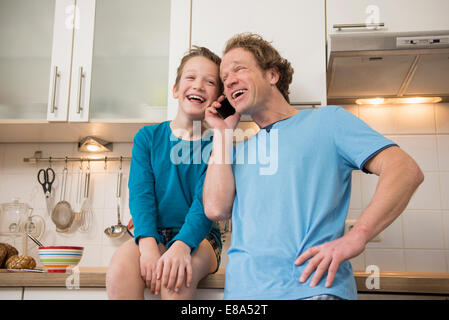 Laughing father and son with cell phone in kitchen - Stock Photo
