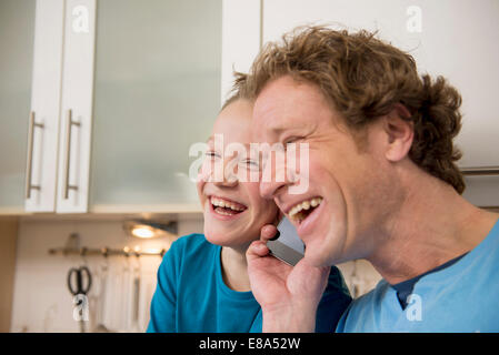 Laughing father and son with cell phone in kitchen