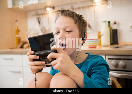 Boy playing video game in kitchen - Stock Photo