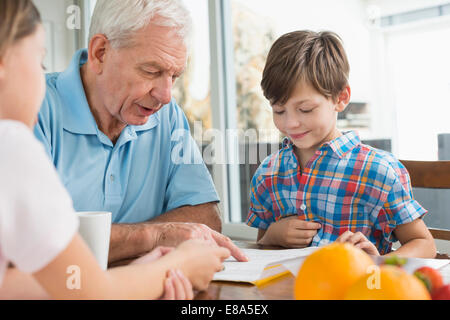 Children doing homework with their grandfather - Stock Photo