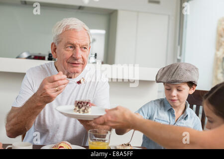 Extended family at table eating cake - Stock Photo