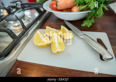 Lemon slices on chopping board with knife, close up - Stock Photo