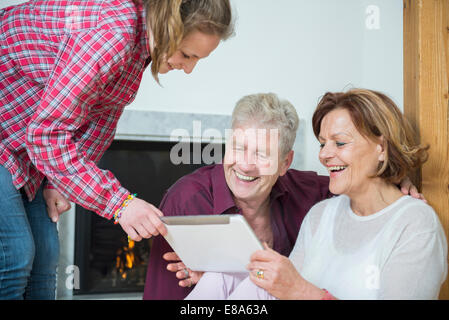 Granddaughter showing something on digital tablet to her grandparents, smiling - Stock Photo