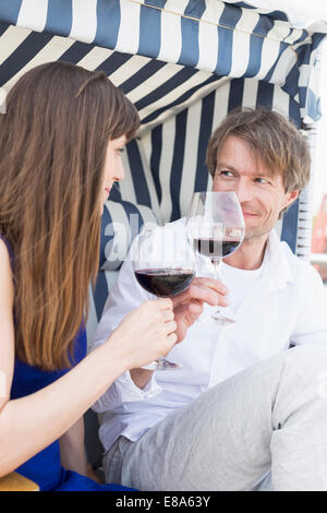 Couple having vine in roofed wicker beach chair, smiling - Stock Photo