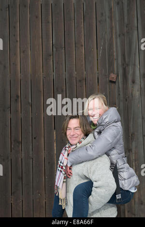 Man giving piggy back ride to woman, smiling, Bavaria, Germany - Stock Photo
