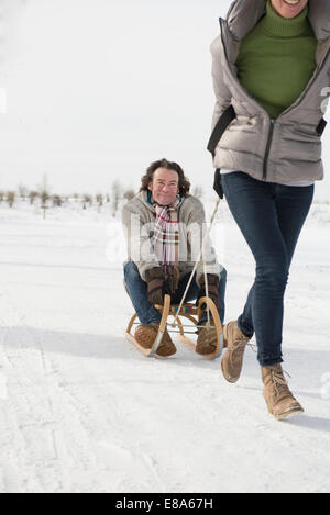 Woman dragging man on sledge in snow, Bavaria, Germany - Stock Photo