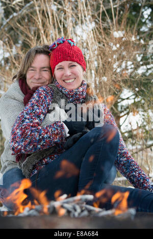 Couple sitting by fire in winter, smiling, Bavaria, Germany - Stock Photo