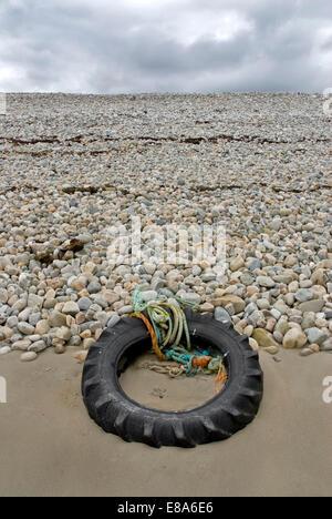 Tractor tyre on a shingle beach, Connemara. - Stock Photo