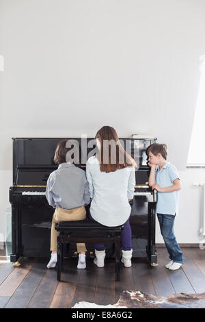 Mother and daughter playing piano while brother is listening - Stock Photo